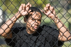 AfAm male behind fence