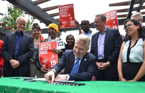 Seattle Mayor Ed Murray signs $15 minimum wage into law as Gordon McHenry, Jr. (5th from left) looks on. (Photo from murray.seattle.gov)